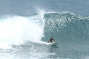 Photo of David Sills - Surfer-Saxophonist sliding left easily outpacing a large cresting wave