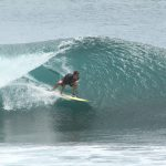 Photo of David Sills - Surfer-Saxophonist crouching low as he runs a tube wave