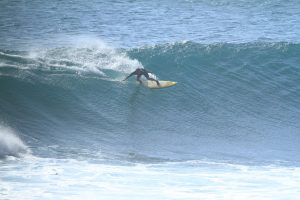 Photo of David Sills - Surfer-Saxophonist riding a wave and leaning way over