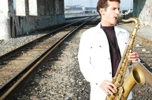 photo of David Sills playing saxophone beside train tracks
